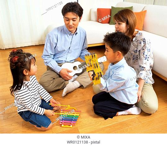 A small girl playing xylophone while family members look at her