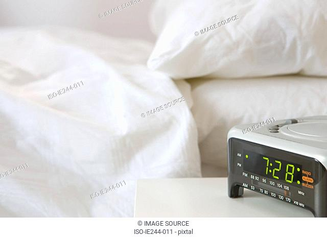 Alarm clock next to a bed
