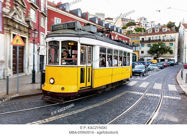 Old tram (blurred motion) in front of colorful city buildings at Largo das Portas do Sol, Alfama district