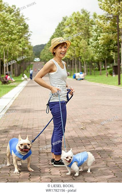 Woman walking two dogs on a paved path