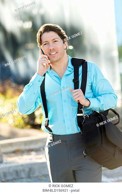 Hispanic businessman talking on cell phone outdoors