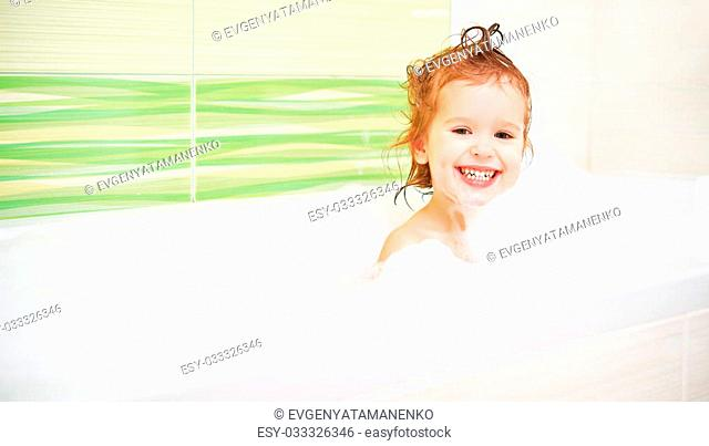 happy child toddler girl bathes in a bath with foam and bubbles