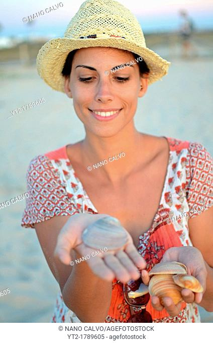 Young woman collecting shells on the beach