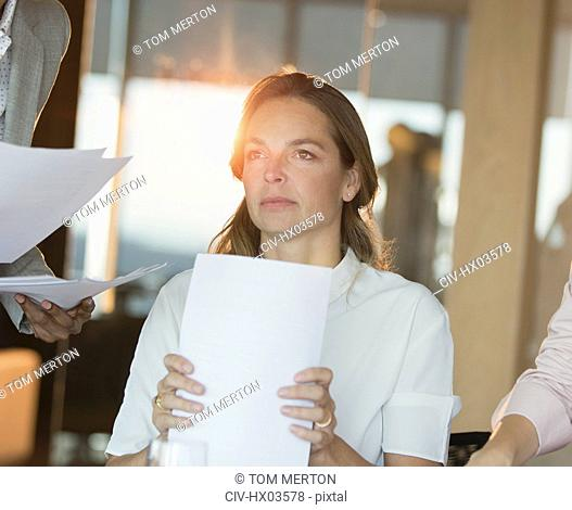 Serious, pensive businesswoman with paperwork looking away in office