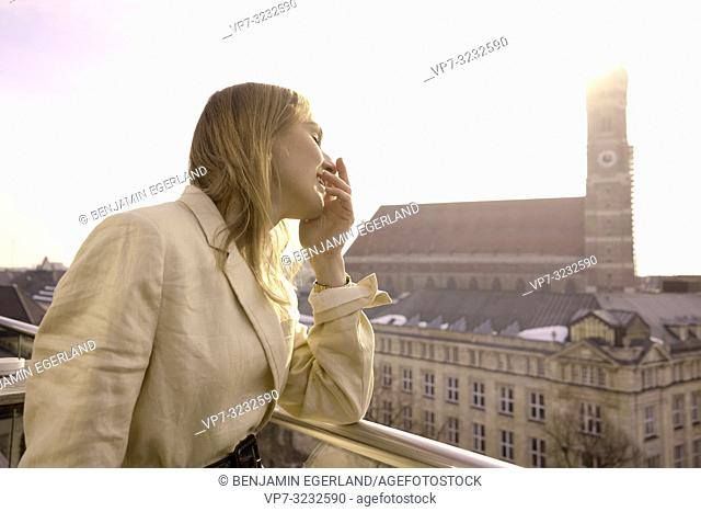 tourist blogger woman on balcony next to church Frauenkirche, Marienkirche, in Munich, Bavaria, Germany