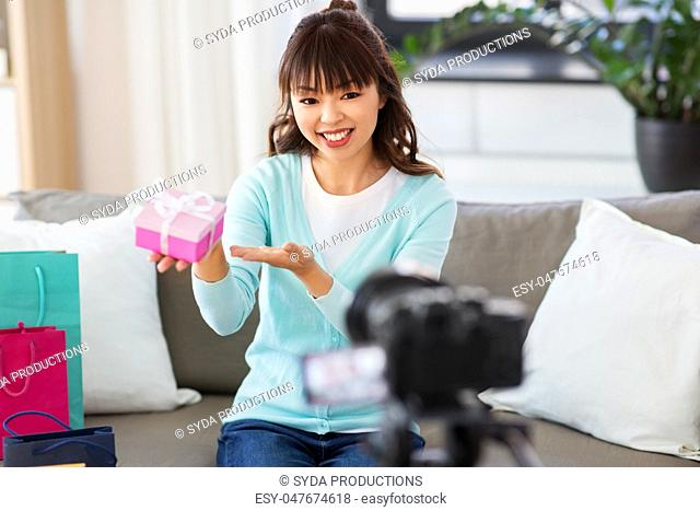 asian female blogger with gift bag recording video