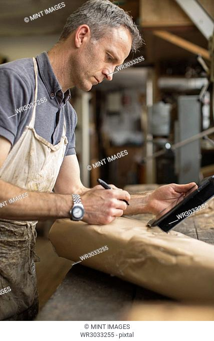 A man in a furniture restoration workshop using a digital tablet, writing on a packet wrapped in brown packaging paper