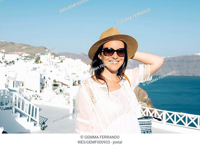 Greece, Santorini, Oia, portrait of smiling woman wearing sunglasses and straw hat