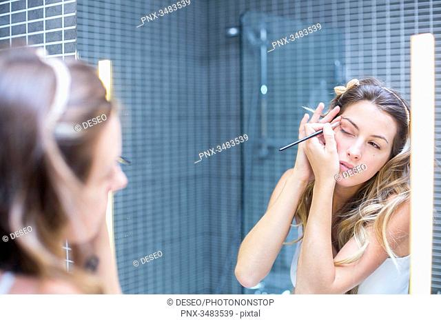 Reflection of a young woman in a mirror applying make-up