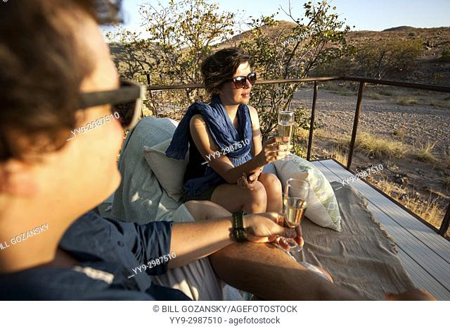 Young couple enjoying a drink at Huab Under Canvas, Damaraland, Namibia, Africa