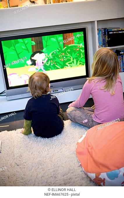 Two children looking at a cartoon on the television Sweden