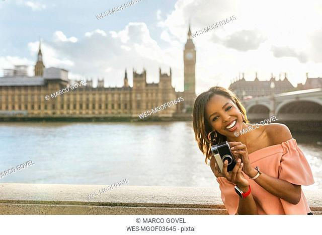 UK, London, happy woman holding a camera near Westminster Bridge