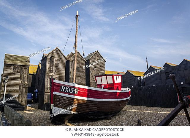 Old boat and iconic Net Shops - tall black wooden sheds for the fishing gear, The Stade area of Hastings Old Town, East Sussex, England, UK