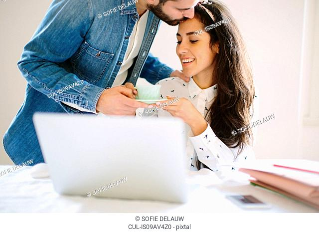 Young man handing coffee to girlfriend working at home on laptop