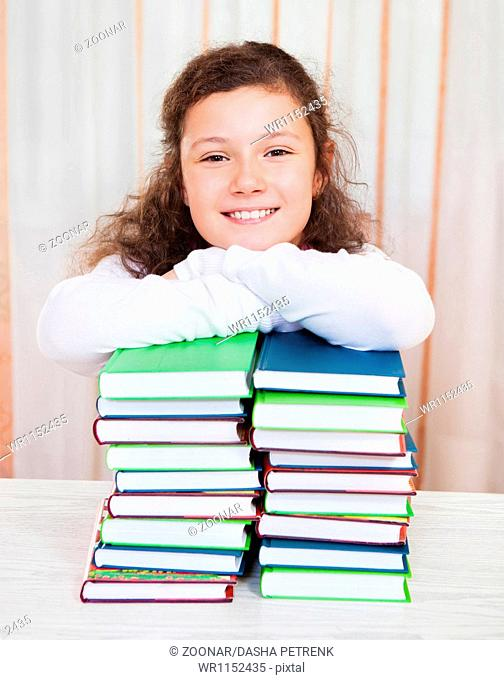 Little girl with pile of books