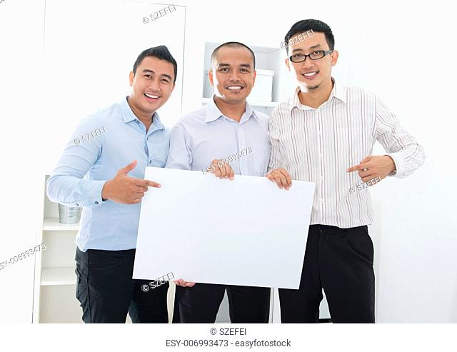 Southeast Asian business team holding a blank banner in office