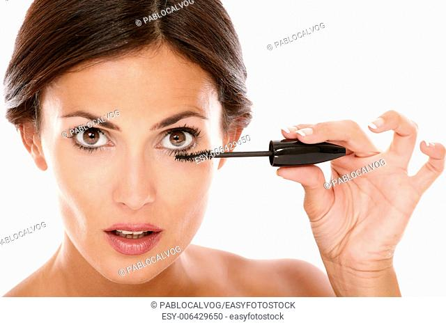Close up portrait of afraid woman with brown eyes applying mascara with nude shoulders while looking at camera on isolated studio
