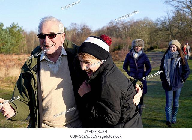 Grandparents and grandchildren walking through field