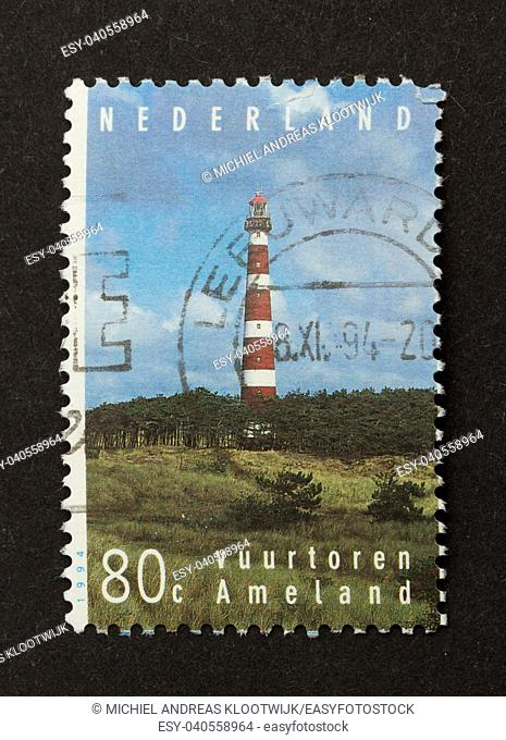 HOLLAND - CIRCA 1980: Stamp printed in the Netherlands shows the lighthouse of the dutch isle of Ameland, circa 1980