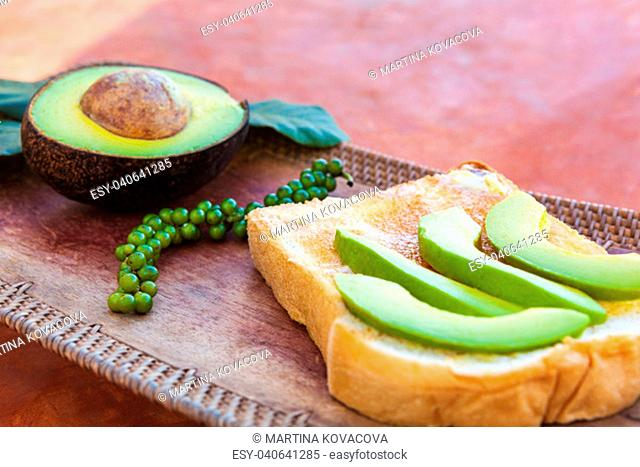 Sliced avocado on toast bread with fresh green peppercorn