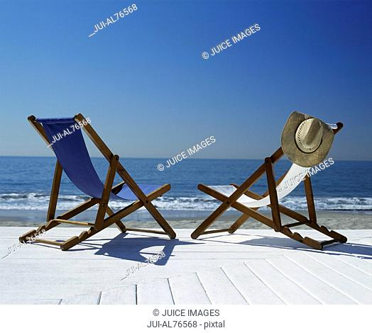 View of two lawn chairs on a deck overlooking the beach