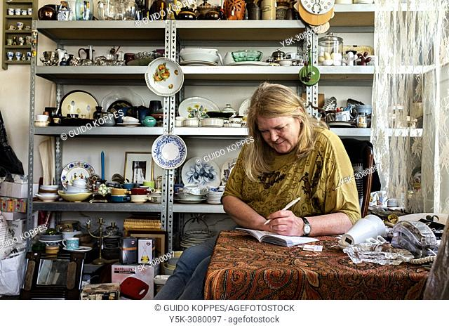 Tilburg, Netherlands. Mature adult, female shop owner killing her time without customers with making a puzzle