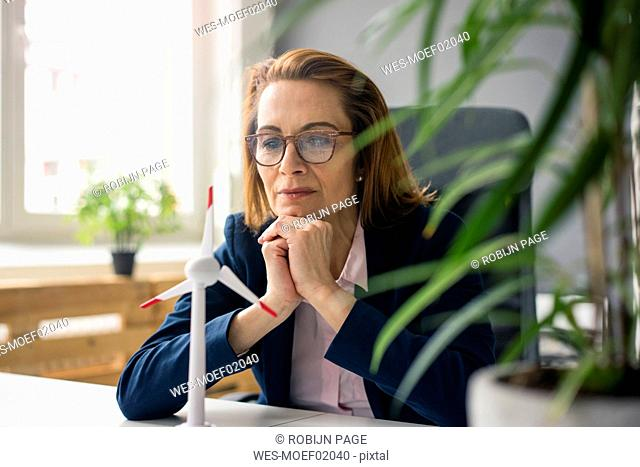 businesswoman sitting at desk, looking at model of a wind wheel