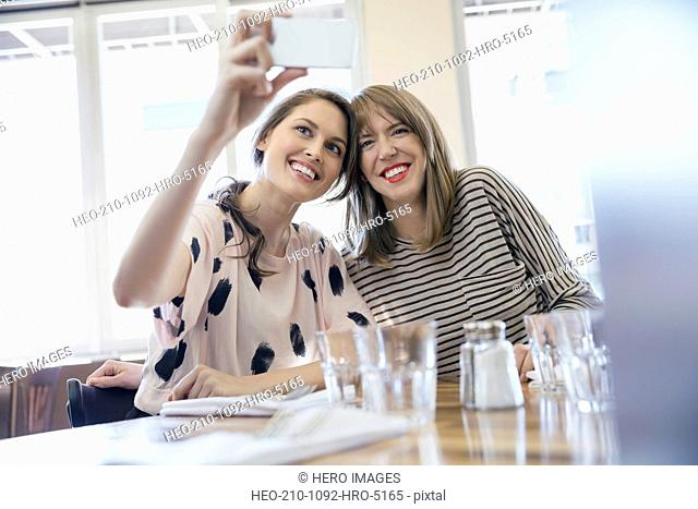 Women taking selfie with camera phone in bistro