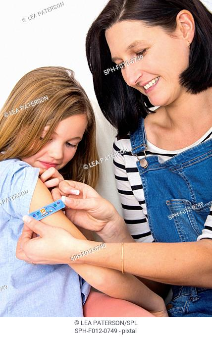Mother applying plaster to daughter