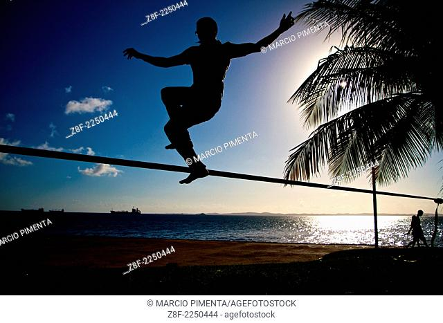 A man practice slackline with the Bay of All Saints in the background. Salvador, Bahia, Brazil