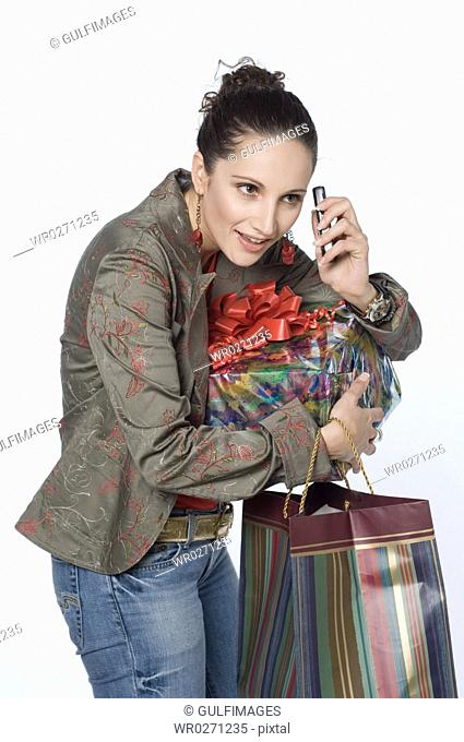 Woman carrying shopping bag, holding mobile phone