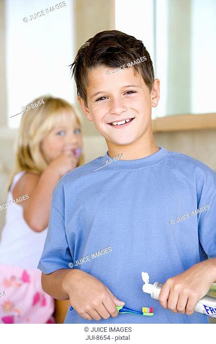 Boy 6-8 applying toothpaste on toothbrush in bathroom, smiling, portrait, sister brushing teeth in background