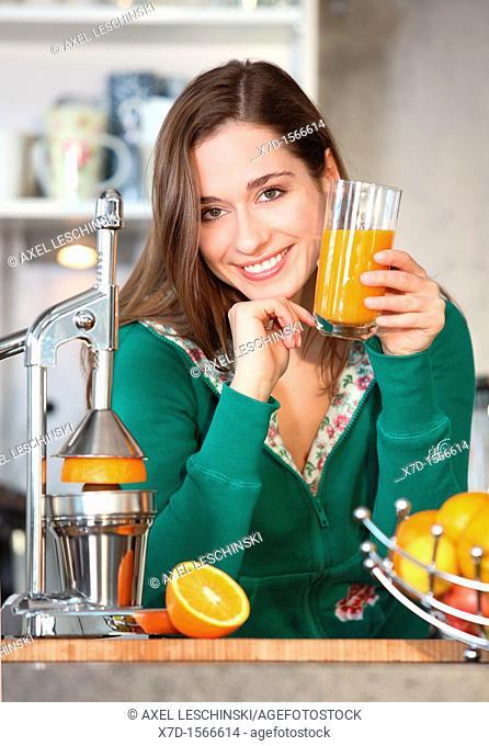 woman standing in kitchen drinking orange juice
