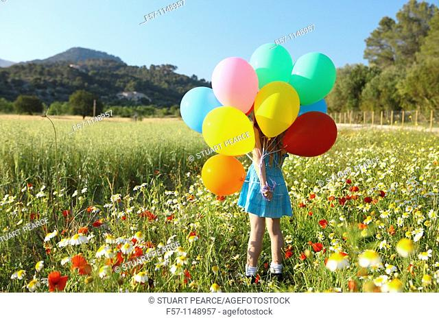 Girl in meadow with balloons