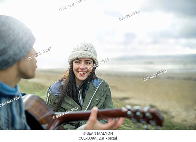 Young man playing guitar, Brean Sands, Somerset, England