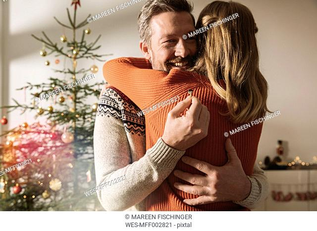 Couple hugging after engagement by Christmas tree