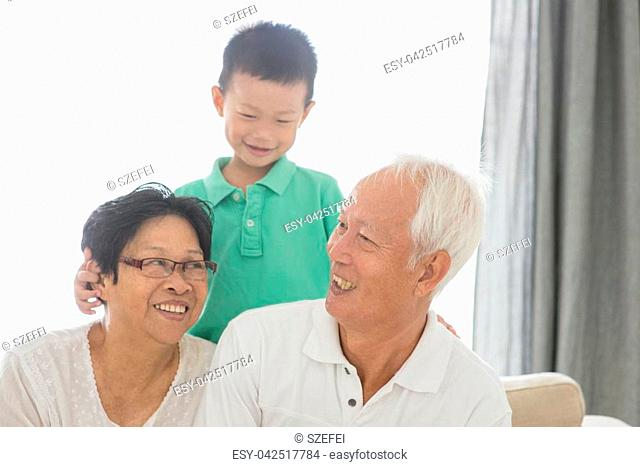 Portrait of happy Asian grandparents and grandson at home, old senior retired people and child indoor lifestyle