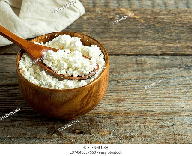 Homemade cottage cheese in a wooden bowl with a spoon on a rustic wooden table