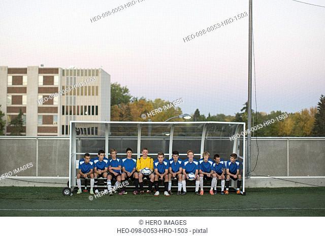 Soccer team sitting on bench together