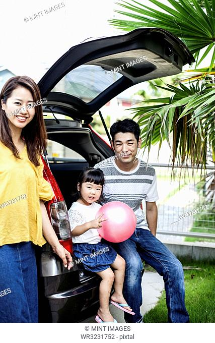 Portrait of Japanese woman, man and girl with pink ball sitting in open boot of car, smiling at camera