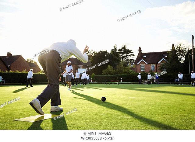 A lawn bowls player standing on a small yellow mat preparing to deliver a bowl down the green, the smooth grass playing surface
