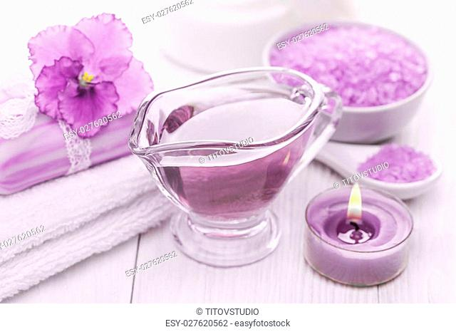 Spa still life of sea salt and essential oils and purple violet flower