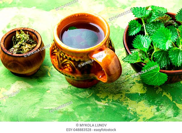 Cup of healthy herbal tea with nettle.Tea with nettles.Fresh stinging nettles