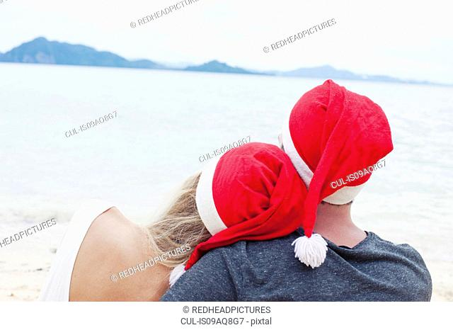 Rear view of young couple wearing santa hats on beach, Kradan, Thailand