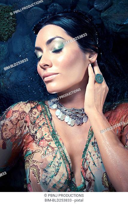 Exotic Hispanic woman laying in water
