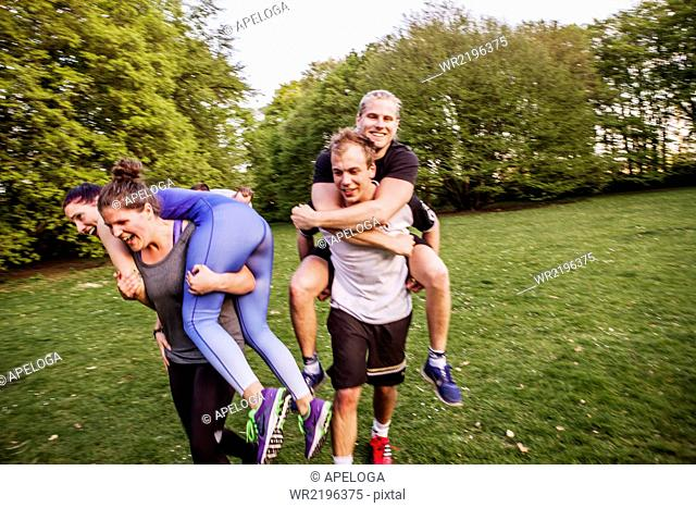 Man and women carrying friends and running on grassy field