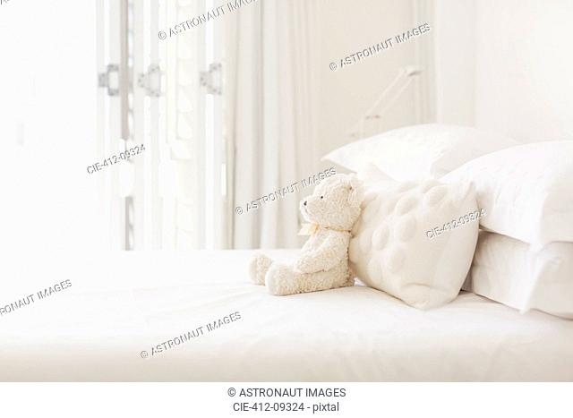 Teddy bear and pillows on white bed