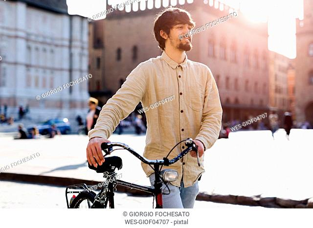 Italy, Bologna, portrait of relaxed young man pushing bicycle in the city