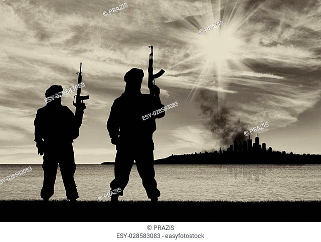Concept of a terrorist attack. Silhouette of terrorists with a rifle on a background of the city in smoke