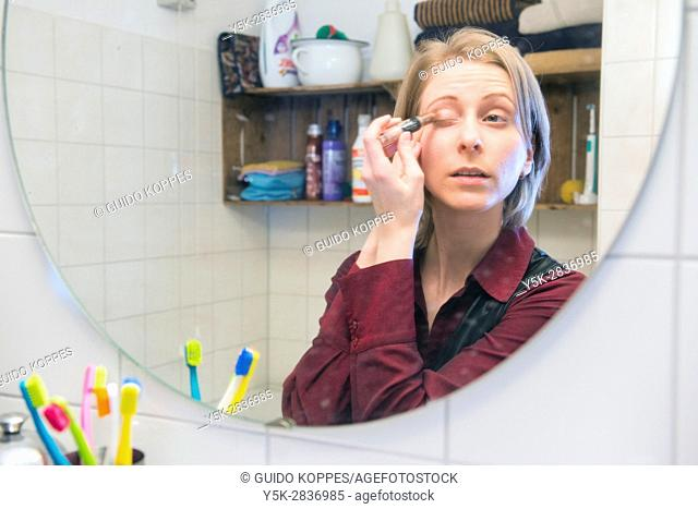 Tilburg, Netherlands. Young adult caucasian woman taking care of her personal presentation and make up inside her bathroom